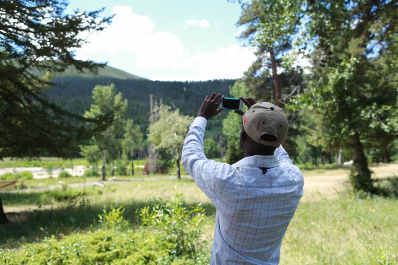 A NASA citizen science project volunteer learns how to measure tree heights.