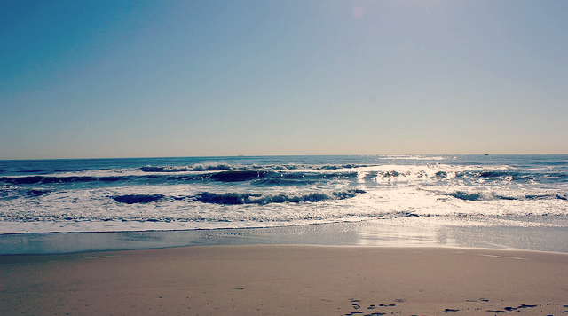 Image alt-text: sunlight reflects off the ocean as it meets the shore Title: Virginia Beach