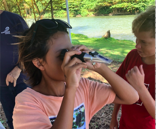A student learns how to measure salinity of a water quality sample with a refractometer. Photo credit: Surfrider Kauai.