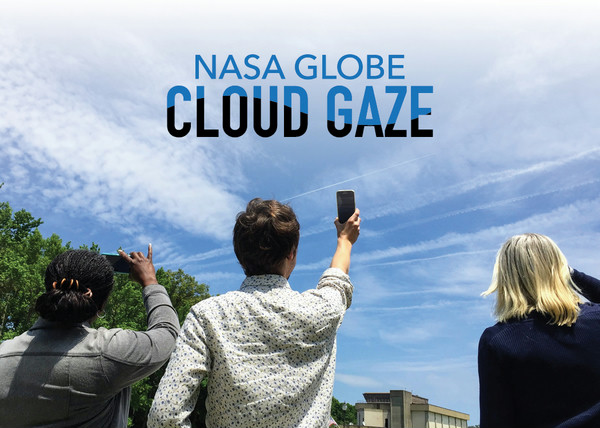 Three people, backs to the camera, take pictures of clouds with their smartphones.