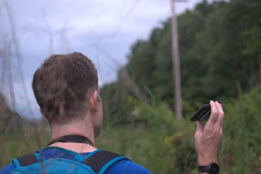 A man listening to bird calls in a field.