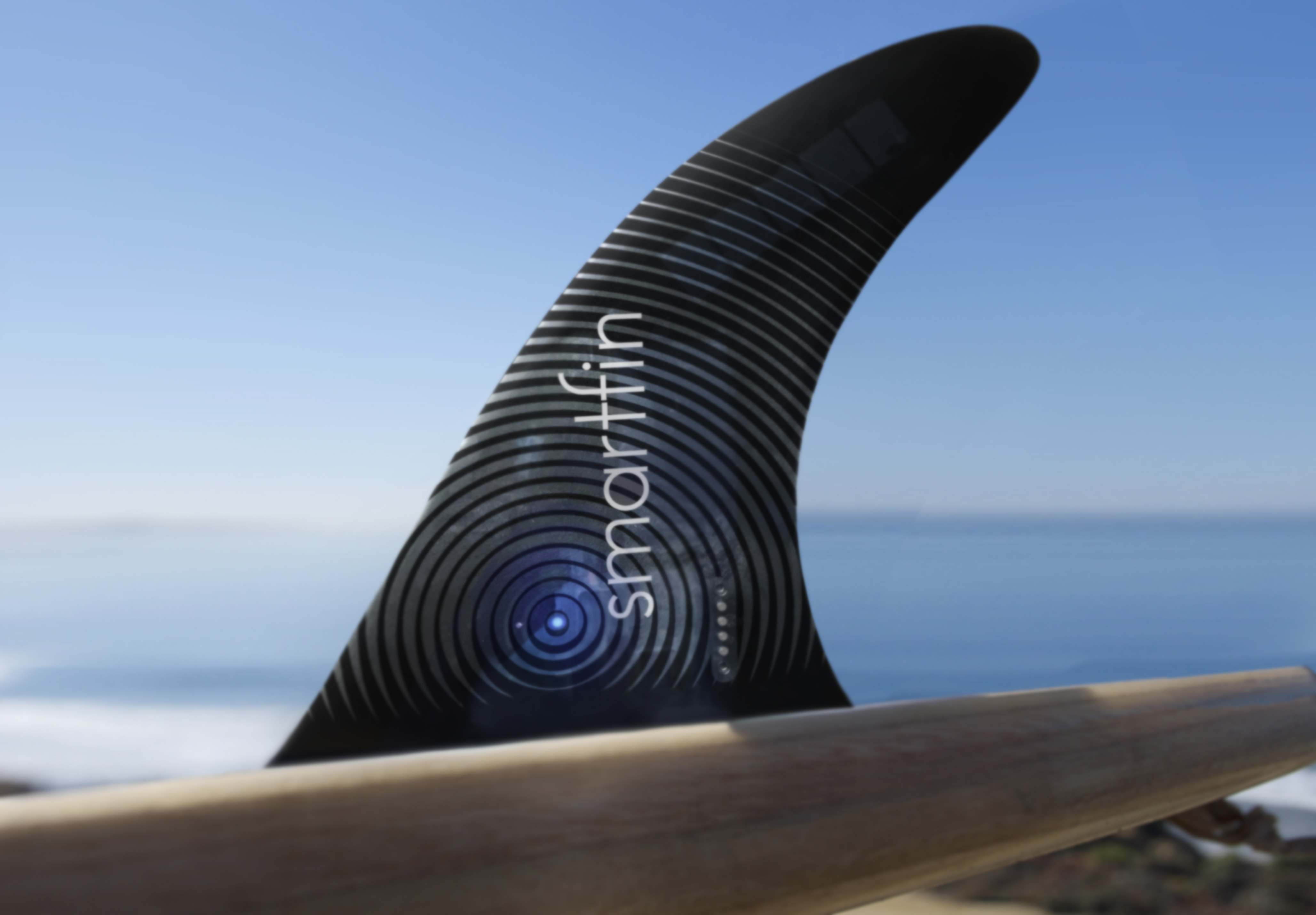 A close-up of a black surfboard fin with the Smartfin logo on it and the ocean in the background.