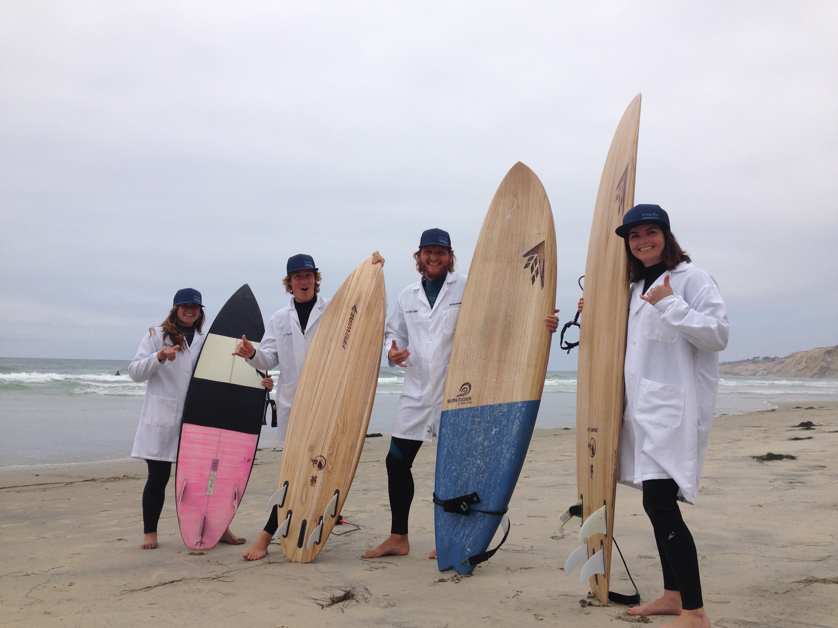 Four Smartfin surfers with surfboards and lab coats pose on the beach.